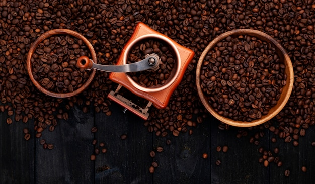 Ground coffee, coffee mill, bowl of roasted coffee beans on black wooden background, top view