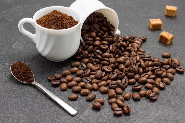 Ground coffee in cup and spoon. roasted coffee beans are scattered from cup onto table. close up.