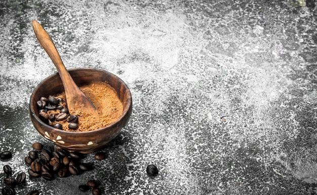 素朴な背景のボウルに挽いたコーヒー