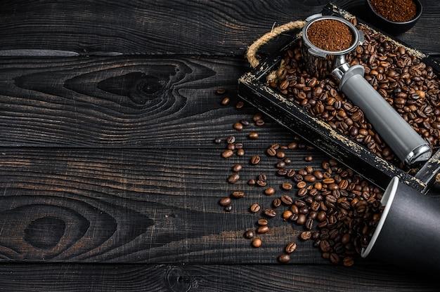 커피 원두가 든 나무 트레이에 에스프레소 용 portafilter의 분쇄 커피