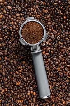 Молотый кофе в portafilter для эспрессо с кофейными зернами.