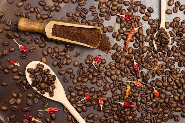 나무 국자에 갈은 커피. 숟가락에 볶은 커피 콩. 테이블에 볶은 커피 콩. 위에 말린 고추 꼬투리.