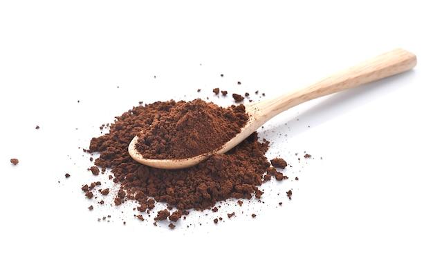 Молотый кофе в деревянной ложке на белом