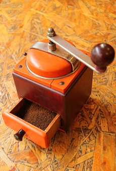Ground coffee in the vibrant color retro coffee grinder ready for homemade coffee