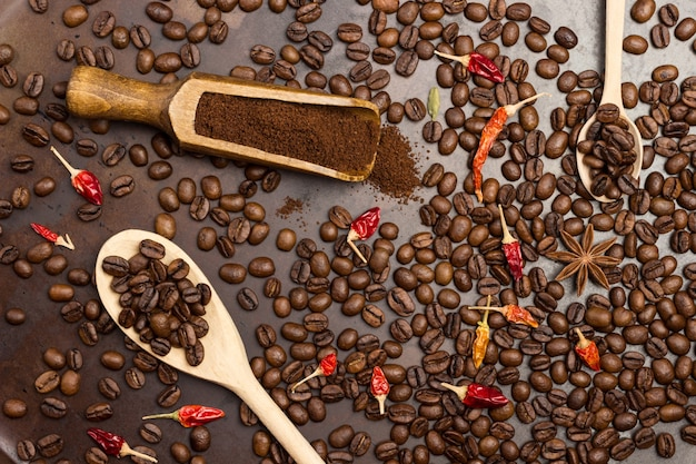 Ground coffee in wooden scoop. roasted coffee beans in spoon. roasted coffee beans on table. dried red pepper pods on top.