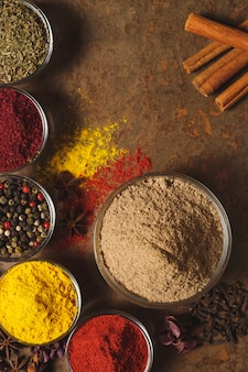 Ground cumin . place for text. different types of spices in a bowl on a stone wall. the view from the top