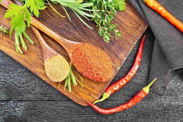 Молотый острый красный перец и паприка в ложках, стручки чили, острая зелень и салфетка на деревянной доске