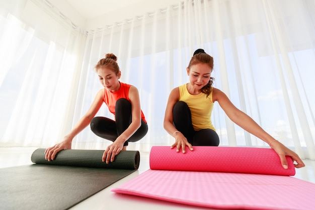 Ground level of asian girlfriends rolling mats and looking at each other at end of yoga session in light studio
