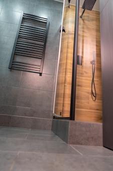 Вид с первого этажа на современный кафельный душ с большой прямоугольной лейкой и полотенцесушителем, установленным на стене.