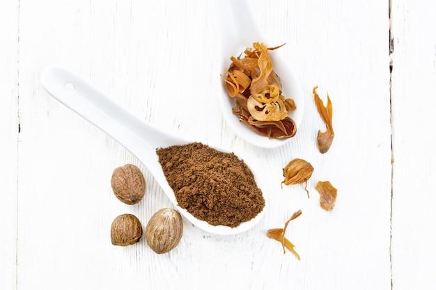 ナツメグと乾燥ナツメグの仮種皮をスプーン2杯で挽き、ナッツ全体を明るい木の板の背景に上から見ます。