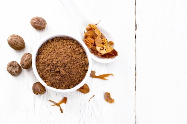 ボウルにナツメグを挽き、スプーンで乾燥したナツメグの仮種皮、木の板の背景にナッツ全体を上から