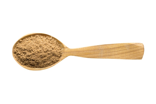 Ground nutmeg powder for adding to food. spice in wooden spoon isolated on white. seasoning of delicious meal.