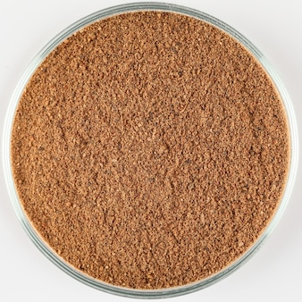 Ground nutmeg powder seasoning in a plate, top view. spice isolated on white