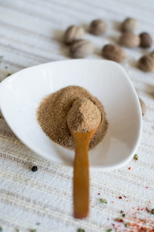 Ground nutmeg in a white bowl with a wooden spoon in it