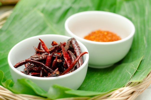 Ground pepper, dried chillies in a white cup.