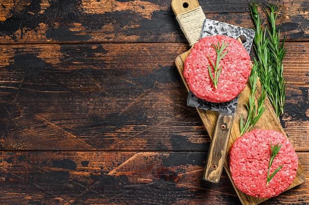 生肉のパテを挽く。調理する準備ができている肉カツ。農場の有機肉。暗い木の背景。上面図。テキスト用のスペース