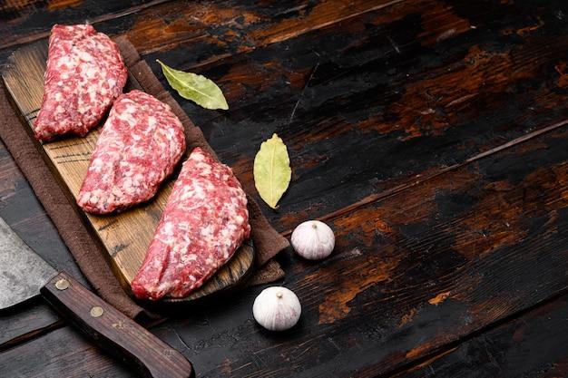 갈은 생고기 패티. 고기 커틀릿 요리 준비. 오래된 어두운 나무 테이블 배경에 있는 농장 유기농 고기 세트, 텍스트 복사 공간