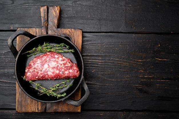生肉のパテを挽く。肉のパテセット、鋳鉄製フライパン、黒い木製のテーブルの背景、上面図フラットレイ、テキスト用のコピースペース