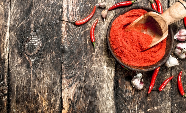 마늘과 함께 그릇에 갈은 붉은 고추. 나무 배경.