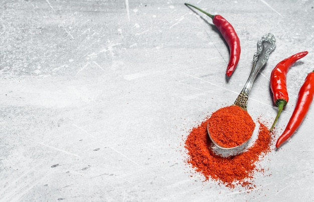 Ground red pepper in a spoon with fresh pepper pods on rustic table