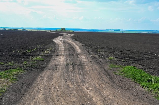 Ground road leaving to the horizon. agriculture plowed field. black soil plowed field. tillage soil prepared for planting crop. fertile soil in organic agricultural farm. l