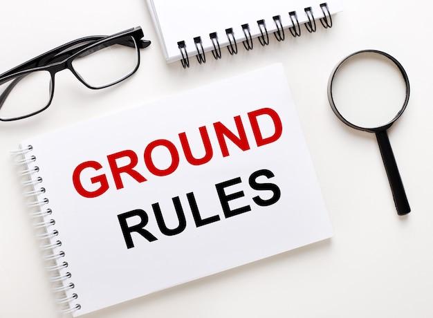 Ground rules는 노트북 근처의 밝은 표면에있는 흰색 노트북, 검은 색 프레임 안경 및 돋보기에 적혀 있습니다.