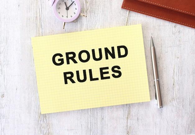 나무 작업 테이블에 누워 노트북에 쓰여진 지상 규칙 텍스트. 비즈니스 개념.
