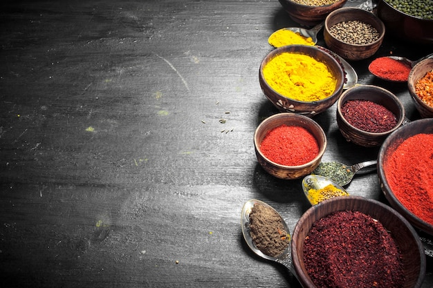 Ground spices in bowls and spoons. on the black chalkboard
