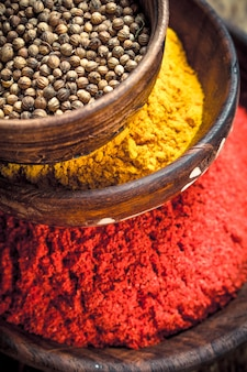Ground spices in bowls. on a wooden background.