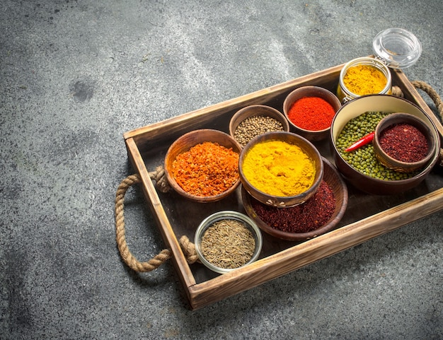 Ground spices in bowls on a wooden tray. on a rustic background.