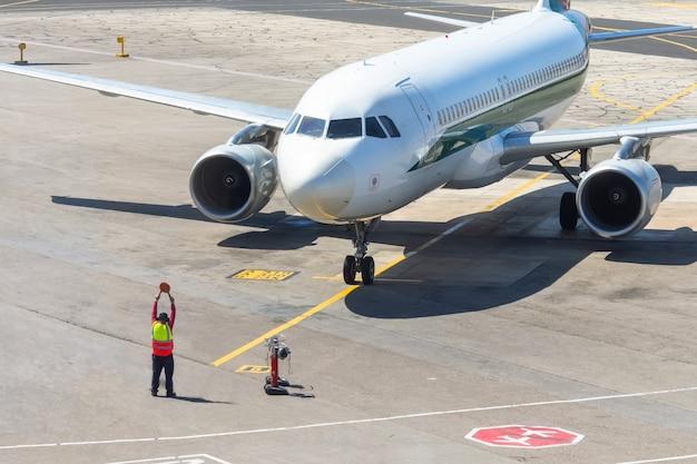 Ground staff airplane marshaller meets passenger plane after landing flight.
