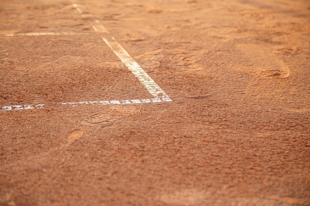 Ground on tennis court with white lines in daylight.