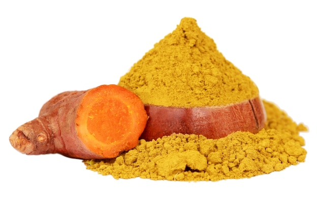 Ground turmeric on a wooden bowl with whole ones on white background