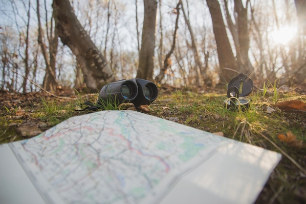 Ground with open map, compass and binoculars