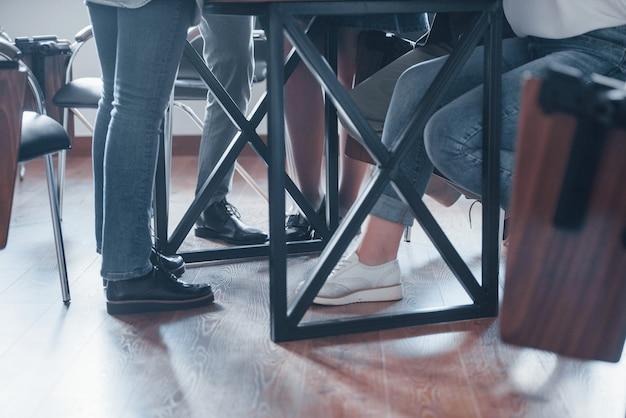 固定ビュー。昼間の近代的な教室でのビジネス会議での人々のグループ