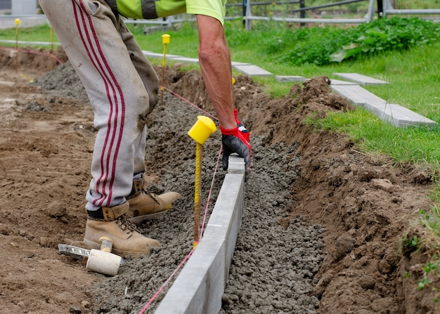 Земляной рабочий укладывает бордюрный бордюр на полусухой бетон по линии струны для отделки дороги