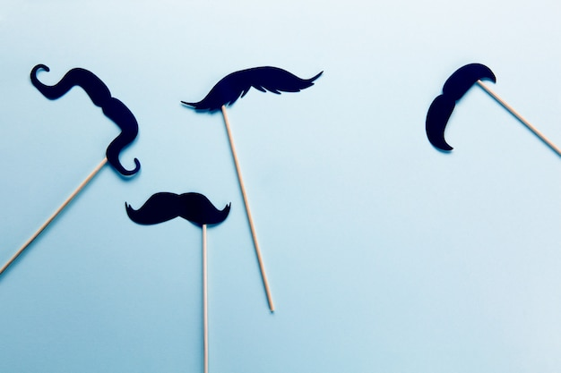 Group of accessories in form of black moustaches on sticks on grey blue with copy space.