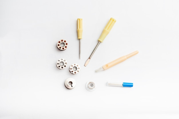 A group of accessories for a sewing machine on a white background