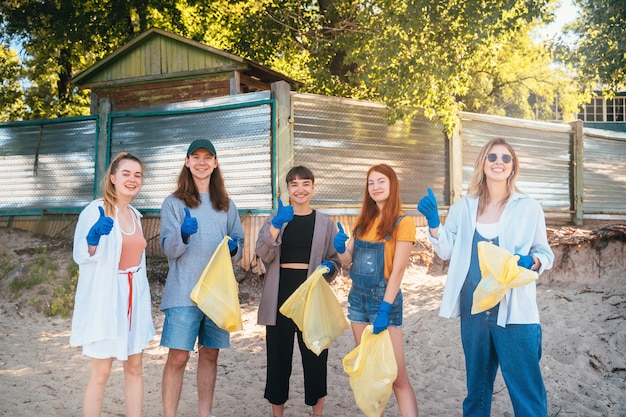 Group of activists friends collecting plastic waste on the beach. guys show thumb up.