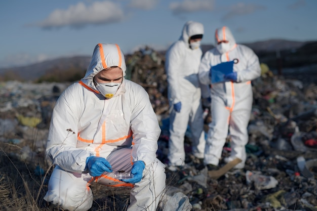 Group of activists with protective masks and suits on landfill, environmental pollution concept.