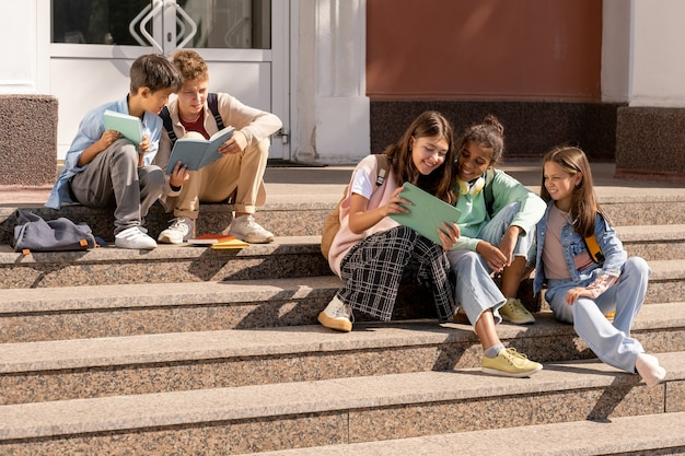 Group of adolescent schoolkids using tablets while sitting on staircase