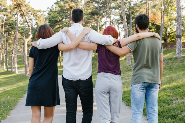 Group of adult friends hugging and walking along road