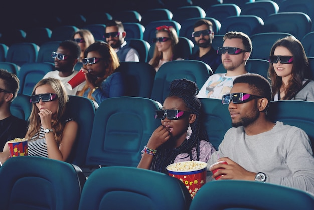 Group of africans and caucasians watching movie in 3d glasses in modern cinema hall.