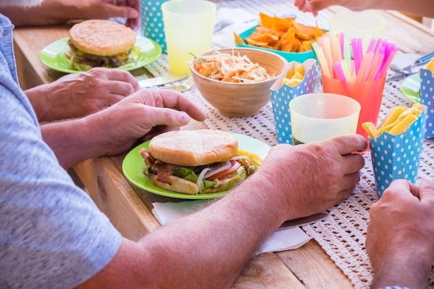 Group of aged caucasian people enjoy together a fast food lunch with hamburgers hand made and french fries on a wooden table - concept of diet and weight loss with unhealthy lfiestyle