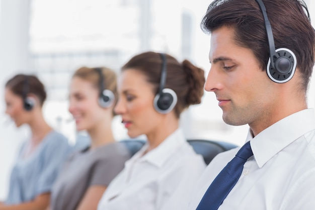 Group of agents sitting in line in a bright call centre Premium Photo