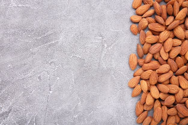 Group of almonds on a grey concrete background