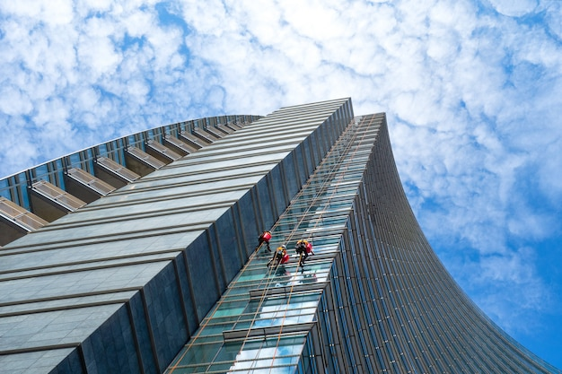 Group of alpinists in service for windows cleaning of skyscrapers buildings