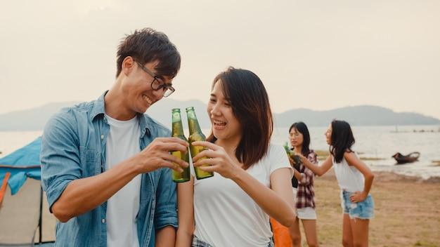 Il gruppo di adolescenti asiatici migliori amici si concentra su una coppia di brindisi con birra e gode di una festa in campeggio con momenti felici insieme accanto alle tende nel parco nazionale