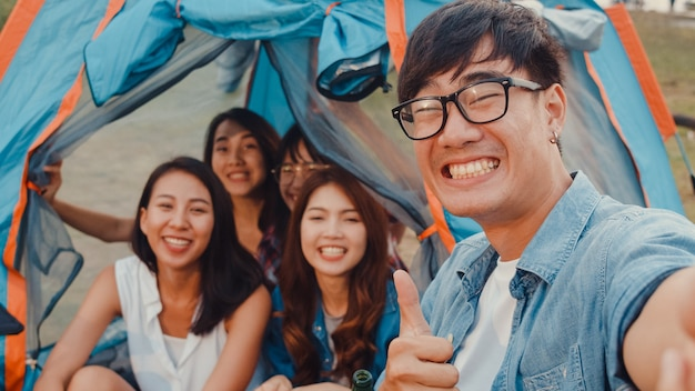 Group of asia best friends teenagers take selfie picture and video with phone camera enjoy happy moments together inside tents in national park