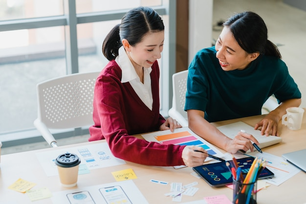 Group of asia young creative people japanese female boss supervisor teaching intern or new employee hispanic girl helping with difficult assignment in modern office. coworker teamwork concept.